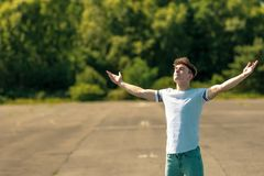 On a warm summer`s afternoon. Young adult male standing outside with arms outstretched enjoying the sunshine Royalty Free Stock Photo