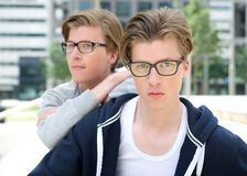 Young adult male twins posing outdoors. Close up portrait of two young adult male twins posing outdoors Royalty Free Stock Photos