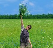 Young adult man with bouquet of wildflowers Stock Photography