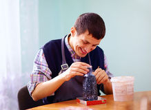 Young adult man with disability engaged in craftsmanship on prac. Tical lesson, in the rehabilitation center Stock Photo