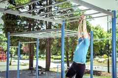 Exercise on monkey bars in park Royalty Free Stock Images