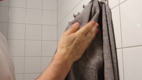 Young adult man dries his hands by a towel at home