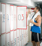 Young adult man drinking water in locker room Stock Images