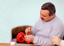 Young adult man engaged in craft work in rehabilitation center Stock Image