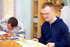 Young adult man engages in self study, in rehabilitation center. Young adult men with disability engages in self study, in rehabilitation center Stock Images