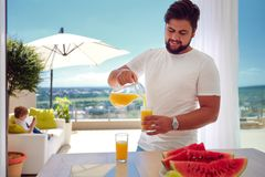 Young adult man, father pouring fresh juice on open space kitchen at sunny summer day Stock Photos