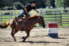 Young adult man galloping during a barrel race Stock Images