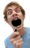 Young adult man holding magnifying glass to mouth Stock Photo