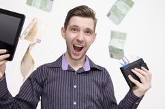 Young adult man holding tablet and credit cards, while money (euros) is falling from air Royalty Free Stock Photo