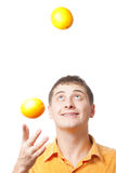 Young adult man juggle with oranges Royalty Free Stock Photo
