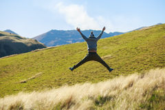 Young adult man jumping on meadow Stock Photos