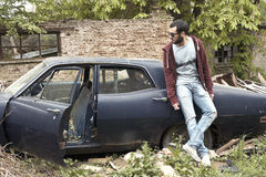 Young adult man leaning on a car Royalty Free Stock Photo