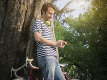 Young adult man messaging on his phone outdoor in the city Royalty Free Stock Photos