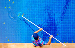 Young adult man, personnel cleaning the pool from leaves. Young man, personnel cleaning the pool from leaves royalty free stock images