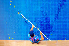 Young adult man, personnel cleaning the pool from leaves. Top view royalty free stock images