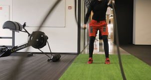 Young adult man practising battle rope exercise during a crossfit workout at the gym. Young adult man doing crossfit workout, man training at the gym working out stock video footage