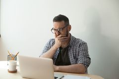 Young adult man reading awful news article in his laptop compute. R. Hand covers his mouth. Receiving news of relative decease concept Royalty Free Stock Photo