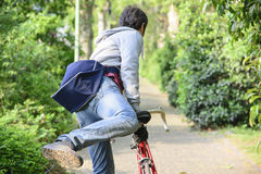 Young adult man riding a bike in the city park Stock Images