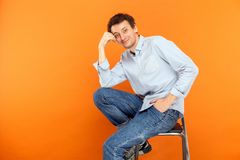 Young adult man sit on chair, touching head, looking at camera a. Nd toothy smile. Studio shot, orange background Stock Image