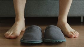 Young adult man sits on a sofa near a slippers - feet level Stock Photo