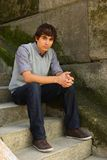 Young adult man sitting. On stone stairs Royalty Free Stock Photo