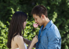 Young Adult man smelling a pink rose from his lady Royalty Free Stock Photos