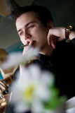 Young adult man smoking in a restaurant Stock Photography