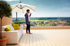 Young adult man standing on rooftop terrace, enjoying beautiful cityscape view stock photography