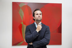 Young adult man thinking in front of painting in art gallery Stock Photography