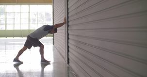 Young adult man warming up stretching during fitness sport workout.Side view .Grunge industrial urban training.4k slow. Motion video stock video footage