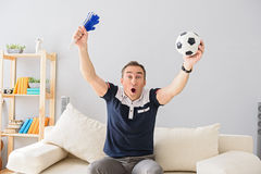 Young adult man watching television. I am the most ardent fan. Shot of handsome adult man celebrating while watching sports match on tv at home, holding football Stock Images