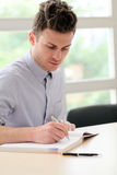 Young adult man writing note Royalty Free Stock Photos