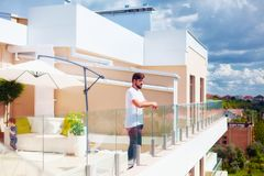 Young adult man enjoying the view from rooftop patio royalty free stock photo