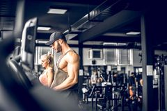 Couple doing treadmill run. Young adult men and women doing running exercise on treadmill in modern fitness center. Toned image Royalty Free Stock Photo