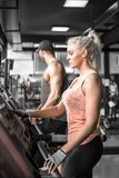 Couple doing treadmill run. Young adult men and women doing running exercise on treadmill in modern fitness center. Toned image Stock Photo