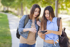 Young Adult Mixed Race Twin Sisters Sharing Cell Phone Experienc Stock Photos