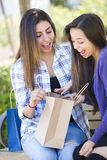 Young Adult Mixed Race Women Looking Into Their Shopping Bags Royalty Free Stock Photo