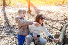 Young adult mother and little daughter walking together in forest or park on bright sunny day. Cute blond baby girl pointing with. Finger somewhere royalty free stock photos