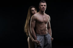 Young adult muscular man and woman. Sexy couple on black background Stock Photography