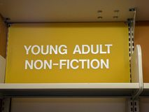 Young adult, non-fiction sign top of library shelf royalty free stock photo