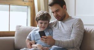 Dad teach kid son using phone having fun on sofa