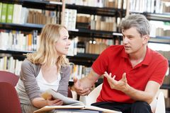 Young adult people reading book in library Stock Photos