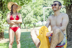 Young adult plays on a spring toy duck. Under his girl& x27;s stern look.  Concept of young people having fun in summertime Royalty Free Stock Image