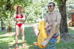 Young adult plays on a spring toy duck. Under his girl& x27;s stern look.  Concept of young people having fun in summertime Stock Image