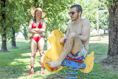 Young adult plays on a spring toy duck. Under his girl& x27;s stern look.  Concept of young people having fun in summertime Royalty Free Stock Photography