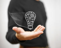 Young adult is presenting light bulb with sprockets royalty free stock photography