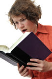 Young Adult reading book. Young adult reading a book closeup with brown eyes. He is shocked by what he is reading Royalty Free Stock Photography