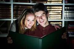 Young adult reading magic book in library Royalty Free Stock Image