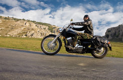 Young adult  rebel biker riding a chopper. Motorcycle in a remote location Royalty Free Stock Image