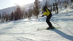 Young adult recreational skier enjoys idyllic perfect weather in cold winter. Skiing alone on perfectly groomed ski. Piste at ski resort. Located at the top of stock video footage